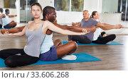 Купить «People doing stretching exercises in pairs», фото № 33606268, снято 30 июля 2018 г. (c) Яков Филимонов / Фотобанк Лори