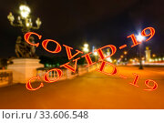 Coronavirus in Paris, France. Covid-19 sign on a blurred background. Concept of COVID pandemic and travel in Europe. The Alexander III bridge at night. Стоковое фото, фотограф Владимир Журавлев / Фотобанк Лори
