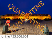Coronavirus in Paris, France. Quarantine sign on a blurred background. Concept of COVID pandemic and travel in Europe. Les Invalides (The National Residence of the Invalids) at night. Стоковое фото, фотограф Владимир Журавлев / Фотобанк Лори