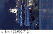 Vertical video evening view passenger Cruise Liner Norwegian Jewel sailing in sea port at night. Редакционное видео, видеограф А. А. Пирагис / Фотобанк Лори
