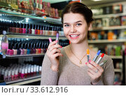 Купить «Smiling woman customer browsing rows of lipstick», фото № 33612916, снято 21 февраля 2017 г. (c) Яков Филимонов / Фотобанк Лори
