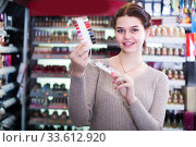 Купить «Young female seller is demonstrating samples of nail polishes», фото № 33612920, снято 21 февраля 2017 г. (c) Яков Филимонов / Фотобанк Лори