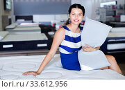 Купить «Young woman is sitting on bed with new pillow in the store.», фото № 33612956, снято 29 августа 2017 г. (c) Яков Филимонов / Фотобанк Лори