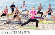 Купить «Sporty people practicing yoga on beach», фото № 33612976, снято 14 июня 2017 г. (c) Яков Филимонов / Фотобанк Лори