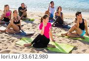 Купить «People exercising yoga poses on beach», фото № 33612980, снято 14 июня 2017 г. (c) Яков Филимонов / Фотобанк Лори
