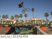 Купить «A BMX Freestyle Team biker jumps off a ramp in a skill demonstration in Huntington Beach, CA.», фото № 33616416, снято 17 ноября 2019 г. (c) age Fotostock / Фотобанк Лори