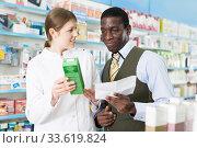 Woman pharmacist talking with man client, picking up prescription. Стоковое фото, фотограф Яков Филимонов / Фотобанк Лори