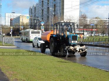 Колесный трактор с бочкой едет по Алтайской улице. Район Гольяново. Город Москва