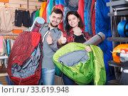 Couple examining touristic equipment items. Стоковое фото, фотограф Яков Филимонов / Фотобанк Лори