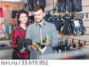 Couple of buyers look at the protective gloves. Стоковое фото, фотограф Яков Филимонов / Фотобанк Лори