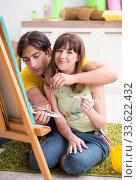 Купить «Young couple enjoying painting at home», фото № 33622432, снято 11 июля 2018 г. (c) Elnur / Фотобанк Лори