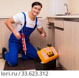 Купить «Young repairman working at the kitchen», фото № 33623312, снято 1 ноября 2016 г. (c) Elnur / Фотобанк Лори