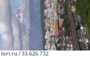 Купить «Vertical video summer cityscape: urban development of city on background of volcano, clouds floating across blue sky, around mountains. Time lapse», видеоролик № 33626732, снято 24 мая 2020 г. (c) А. А. Пирагис / Фотобанк Лори