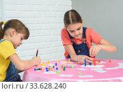 Купить «Две сестры играют в настольную игру», фото № 33628240, снято 5 апреля 2020 г. (c) Иванов Алексей / Фотобанк Лори