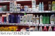 Купить «Variety of hair care products on rack in supermarket», видеоролик № 33629212, снято 7 ноября 2019 г. (c) Яков Филимонов / Фотобанк Лори