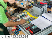 Купить «Electrician assembling industrial electric cabinet in workshop», фото № 33633524, снято 3 июня 2020 г. (c) Matej Kastelic / Фотобанк Лори