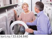 Купить «attentive mature couple chooses washing machine for their house in shop of household appliances», фото № 33634840, снято 30 июня 2020 г. (c) Яков Филимонов / Фотобанк Лори