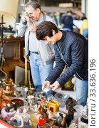 Купить «concentrated elderly woman choosing interesting souvenirs at flea market», фото № 33636196, снято 23 октября 2017 г. (c) Яков Филимонов / Фотобанк Лори
