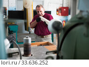 Купить «Positive craftsman working on a thicknessing machine», фото № 33636252, снято 13 июля 2020 г. (c) Яков Филимонов / Фотобанк Лори