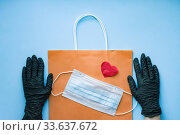 Купить «Hands in black surgical glove holding paper bag with mask and heart. Home delivery precaution measures against COVID-19 with love, Gift bag delivered without direct contact.», фото № 33637672, снято 26 апреля 2020 г. (c) Papoyan Irina / Фотобанк Лори
