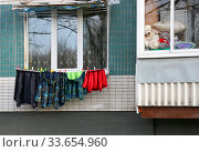 Детские куртки сохнут на веревке под окном квартиры (2018 год). Редакционное фото, фотограф Щеголева Ольга / Фотобанк Лори