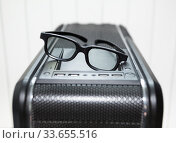 Black eyeglasses is on top of PC tower case with usb connection sockets, power and reset buttons, close-up view. Стоковое фото, фотограф Кекяляйнен Андрей / Фотобанк Лори
