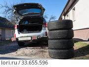 Manual tire change in spring season, summer wheels are ready to install on suv car. Стоковое фото, фотограф Кекяляйнен Андрей / Фотобанк Лори