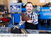 Positive male worker showing fixed shoes. Стоковое фото, фотограф Яков Филимонов / Фотобанк Лори