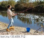 Купить «Adult man standing near river and pulling fish expressing emotions of dedication», фото № 33659712, снято 15 марта 2019 г. (c) Яков Филимонов / Фотобанк Лори