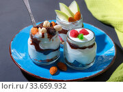 Sweet tasty milk curd creamy food in a glass jar of homemade breakfast. Cheesecake, English Trifle, Eton dessert, tiramisu, zuppa Inglese with nuts, almonds, cashews, hazelnuts, candied fruits and chocolate sauce. Стоковое фото, фотограф Светлана Евграфова / Фотобанк Лори