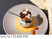 Купить «Sweet tasty milk curd creamy food in a glass jar of homemade breakfast. Cheesecake, English Trifle, Eton dessert, tiramisu, zuppa Inglese with nuts, almonds, cashews, hazelnuts, candied fruits and chocolate sauce», фото № 33659976, снято 14 декабря 2019 г. (c) Светлана Евграфова / Фотобанк Лори
