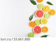 Купить «Sliced slices of citrus fruits laid out on a white table.», фото № 33661880, снято 6 апреля 2020 г. (c) Евдокимов Максим / Фотобанк Лори