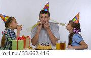 Дети и папа весело дуют в дуделки на праздничном ужине. Стоковое видео, видеограф Иванов Алексей / Фотобанк Лори