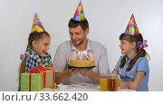 Папа показывает детям праздничный торт с зажженными свечами. Стоковое видео, видеограф Иванов Алексей / Фотобанк Лори