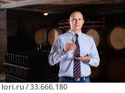 Confident winemaker offering glass of white sparkling wine for tasting in wine cellar. Стоковое фото, фотограф Яков Филимонов / Фотобанк Лори