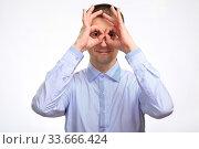 Купить «successful happy man shows the gesture OK with two hands, in a blue light casual shirt, staring at the camera. Isolated», фото № 33666424, снято 22 апреля 2020 г. (c) Владимир Арсентьев / Фотобанк Лори