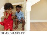 Купить «Mixed race girl and her younger brother using phone at home», фото № 33666544, снято 28 ноября 2019 г. (c) Wavebreak Media / Фотобанк Лори