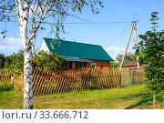 Купить «Beautiful summer country wooden house with an emerald roof, fence, birch, maple», фото № 33666712, снято 23 августа 2015 г. (c) Ирина Мойсеева / Фотобанк Лори