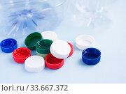 Купить «Colorful plastic caps against bottles. Plastic wrapping rubbish on blue background. Concept of environmental pollution», фото № 33667372, снято 30 апреля 2020 г. (c) Papoyan Irina / Фотобанк Лори