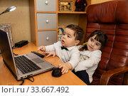 Купить «Маленькие дети смотрят в ноутбук. Офис родителей дома.», фото № 33667492, снято 28 января 2018 г. (c) Светлана Голинкевич / Фотобанк Лори
