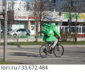 """Купить «Курьер сервиса быстрой доставки еды """"Delivery Club"""" едет на велосипеде по Хабаровской улице в дни самоизоляции при коронавирусе COVID-19. Район Гольяново. Город Москва», эксклюзивное фото № 33672484, снято 26 апреля 2020 г. (c) lana1501 / Фотобанк Лори"""