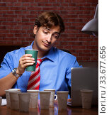 Young employee drinking coffee working at night shift. Стоковое фото, фотограф Elnur / Фотобанк Лори