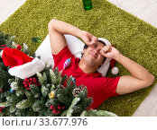 Купить «Young man drunk at home after christmas party», фото № 33677976, снято 17 июля 2018 г. (c) Elnur / Фотобанк Лори