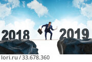 Купить «Businessman balancing between 2018 and 2018 years», фото № 33678360, снято 5 июля 2020 г. (c) Elnur / Фотобанк Лори