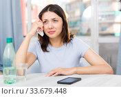 Купить «Unhappy young female student sitting with glass of water», фото № 33679448, снято 18 апреля 2018 г. (c) Яков Филимонов / Фотобанк Лори