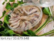 Sliced pickled herring in plastic jar and fresh parsley on the table. Стоковое фото, фотограф Яков Филимонов / Фотобанк Лори