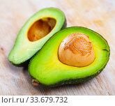 Купить «Close up of cut avocado with bone at wooden table», фото № 33679732, снято 11 июля 2020 г. (c) Яков Филимонов / Фотобанк Лори