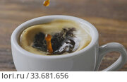 Купить «Close-up in a cup of fragrant espresso with foam fall coffee splash on a brown wooden table. Slow motion, Full HD video, 240fps, 1080p.», видеоролик № 33681656, снято 14 марта 2019 г. (c) Ярослав Данильченко / Фотобанк Лори