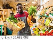 Greengrocery owner offering carrots for sale. Стоковое фото, фотограф Яков Филимонов / Фотобанк Лори