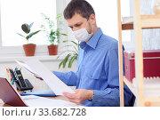 Купить «Офисный служащий в защитной медицинской маске работает с документами в офисе», фото № 33682728, снято 3 мая 2020 г. (c) Иванов Алексей / Фотобанк Лори